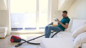 Man with tablet pc and vacuum cleaner at home. Cleaning, household and technology concept - happy man with tablet pc computer and vacuum cleaner at home stock video