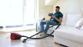 Man with tablet pc and vacuum cleaner at home. Cleaning, household and technology concept - happy man with tablet pc computer and vacuum cleaner at home stock video footage