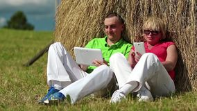 Man with Tablet-PC and woman with smartphone sits near a haystack stock video