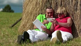 Man with Tablet-PC and woman with smartphone sits near a haystack stock footage