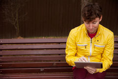 Man with tablet sits on bench in the Park Royalty Free Stock Image