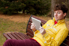Man with tablet sits in Park Royalty Free Stock Photo
