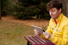 Man with tablet sits in the Park Stock Photo