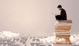 Man with tablet sitting on books. A businessman with laptop tablet in elegant suit sitting on a stack of books on top of sandy labirynth background concept Royalty Free Stock Images