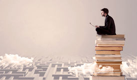 Man with tablet sitting on books Stock Photography