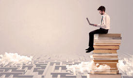 Man with tablet sitting on books. A businessman with laptop tablet in elegant suit sitting on a stack of books on top of sandy labirynth background concept Stock Photo
