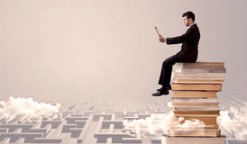 Man with tablet sitting on books. A businessman with laptop tablet in elegant suit sitting on a stack of books on top of sandy labirynth background concept Royalty Free Stock Photos