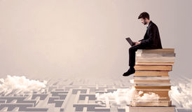 Man with tablet sitting on books. A businessman with laptop tablet in elegant suit sitting on a stack of books on top of sandy labirynth background concept Stock Photography