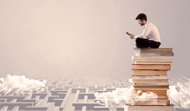 Man with tablet sitting on books Royalty Free Stock Images