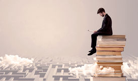 Man with tablet sitting on books. A businessman with laptop tablet in elegant suit sitting on a stack of books on top of sandy labirynth background concept Stock Image