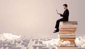 Man with tablet sitting on books. A businessman with laptop tablet in elegant suit sitting on a stack of books on top of sandy labirynth background concept Royalty Free Stock Photo