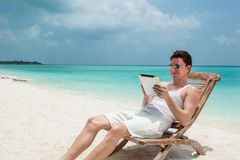 Man with tablet sitting on chair at the beach Royalty Free Stock Photography