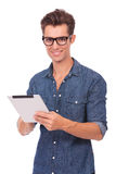 Man with tablet smiles at you. Casual young man working something on his tablet and smiling at the camera. isolated on a white background Stock Images