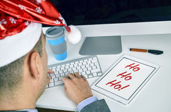 Man with a tablet with text ho ho ho in his office Stock Image