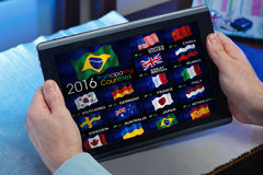 Man on tablet watching a channel of Olympics sports on TV online. Man with device browsing a web page with Flags of countries on the occasion of the Olympics Royalty Free Stock Photos