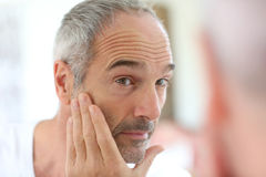 Man tacking care of skin. Mature man in front of mirror applying cosmetics Stock Images
