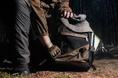 Camping tactical gear in woods. Man in tactical outfit holding a knife and kneeling for backpack with camping and tactical gear on night forest background Royalty Free Stock Photo