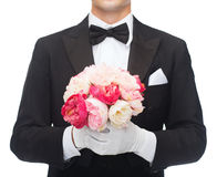 Man in tail-coat with flower bouquet Royalty Free Stock Photos