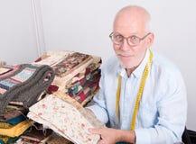 Man tailor choosing fabric. A mature man tailor choosing  some fabric Stock Photo