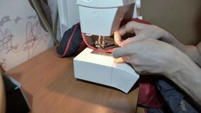 Man tailor sews a zipper on a jacket with a sewing machine.