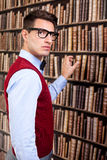 Man take a book. In library and looking at camera Royalty Free Stock Photo