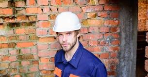 Man take break working day at construction site. Builder helmet construction site sit relaxing lean brick wall. Guy stock photo