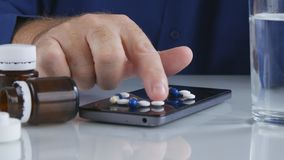 Man Take Colorful Pills from Cellphone Screen Surface royalty free stock images