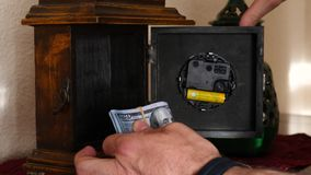 Man take dollars hidden in a clock on top of a piece of furniture stock footage