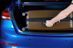 Man take luggage bag from car trunk. Man take luggage bag from modern car trunk close-up. Hand putting suitcase in blue modern car Stock Images