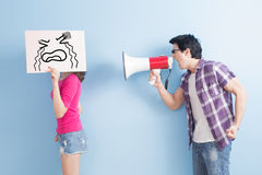 Man take the microphone. Shout to women angrily  isolated on blue background Stock Photography
