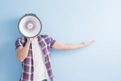Man take microphone. And show something to you on blue background royalty free stock photo