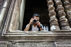 A Man Take a photo through the window at Angkor Thom Temple royalty free stock photos
