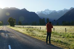 Man take photograph of Mount Cook New Zealand in the morning. Man take photograph of Mount Cook in New Zealand in the morning Stock Photos
