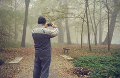 Man take a picture with his phone in the forest Royalty Free Stock Image