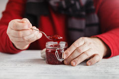 Man take raspberry jam from glass jar on wooden table Stock Photo