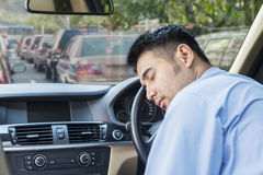 Man take a rest in traffic jam. Tired young businessman driving a car and take a rest in the traffic jam Royalty Free Stock Photo