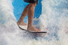 Man take wake surf, riding a surfboard or foot board along an outdoor water slide set up stock images