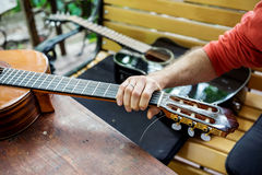 Man takes acoustic guitar. Man takes a classical acoustic guitar in the hand, lying on the wooden table Stock Photos