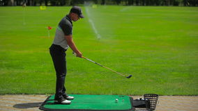 Man takes aim to hit the ball with a club stock footage