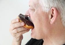 Man takes bite of doughnut Stock Photo