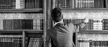 Man takes book from bookcase. Student stands in library and choose book. Guy in smart suit reads near bookcase. Study. Learn, education, research, history stock photography