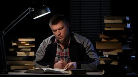 Man takes a book and writes the information itself. Black background stock video footage