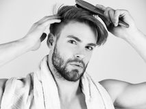 Man takes care of his hair. Bearded man with bathing towel on neck combing healthy hair. Man takes care of his hair. Bearded man or handsome macho with bathing stock photography