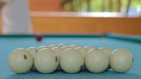 The man takes the cue and starts the game in Russian billiards. The player is preparing to break the pyramid from the balls stock video