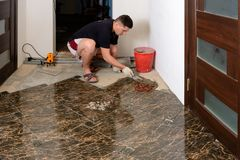 A man takes extra glue to install a ceramic brown tile in a small room stock photography