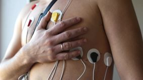 A man takes his hand in the heart while standing in the sensors of the holter. HD