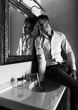 Man takes a look at himself in the mirror. Royalty Free Stock Photo