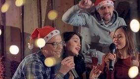 A man joins two singing women at a Christmas party. stock footage