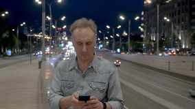 Man takes mobile phone against driving cars at night. Mature man takes mobile phone and reads text against cars driving to tunnel underpass on night city street stock video