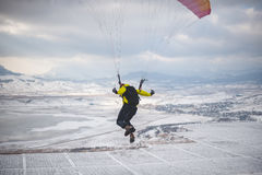 Man takes off with the speedglider from the mountain. Royalty Free Stock Images